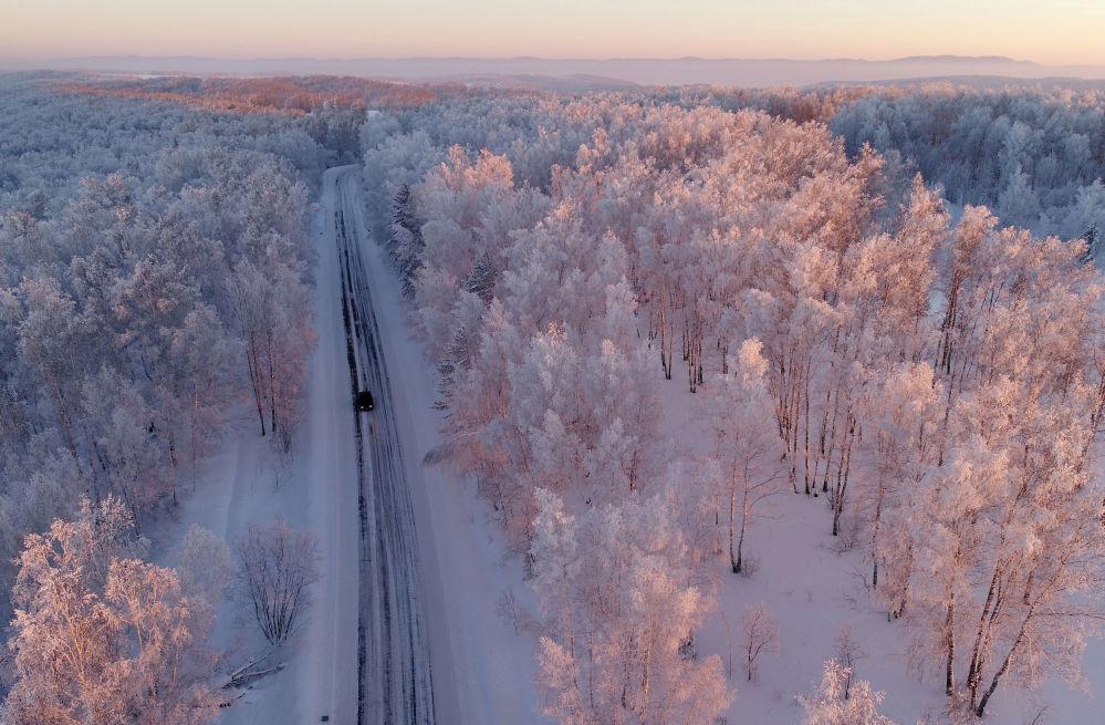 Машина едет по трассе вдоль заснеженного леса на закате, Красноярский край