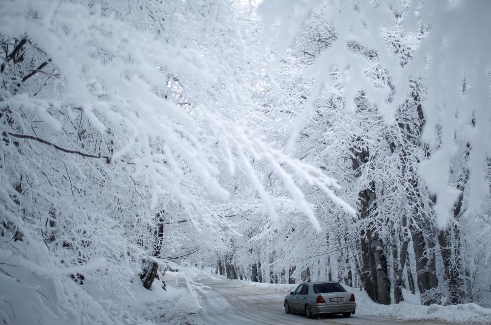 Автомобиль едет по заснеженной дороге близ Тбилиси, Грузия