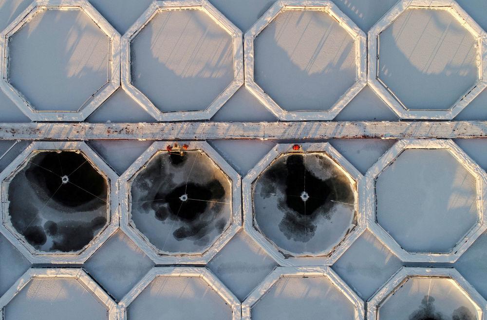 Сотрудники рыбной фермы компании Малтат на замерзшей реке Енисей близ села Приморск Красноярского края, Россия