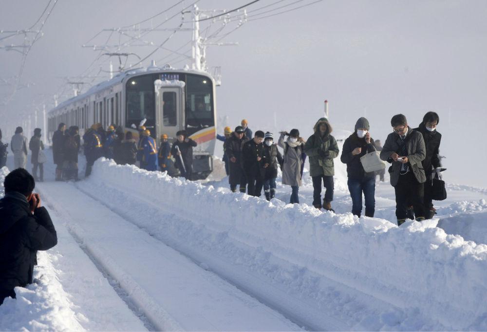 Поезд застрял на перегоне между станциями из-за сильного снегопада в префектуре Ниигата, Япония