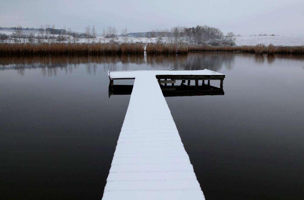Покрытый снегом пирс виден на озере близ от деревни Этьек, Венгрия