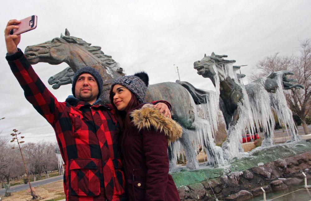 Пара делает селфи перед памятником, покрытым льдом, после похолодания в Сьюдад-Хуаресе, Мексика