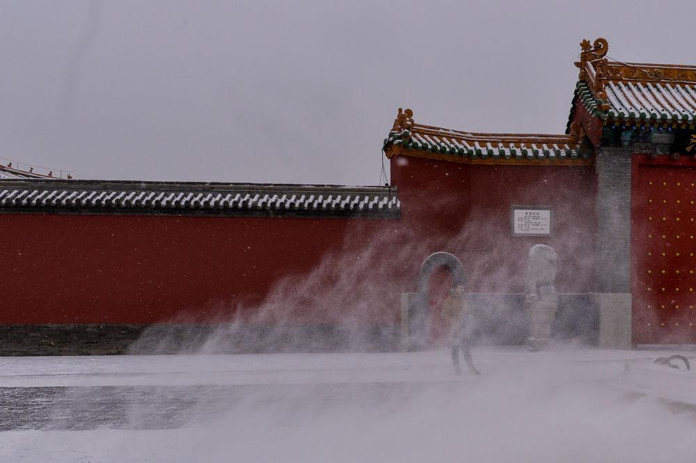 Китайский турист стоит у Императорского дворца во время снегопада в Шэньяне