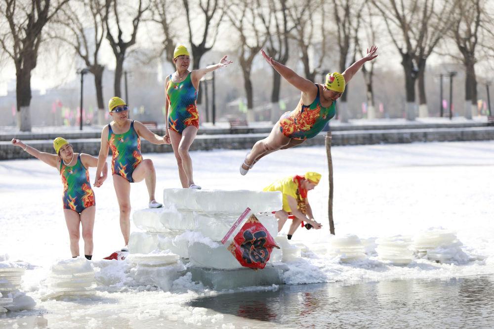 Женщина ныряет в озеро в северо-восточной провинции Ляонин в Китае