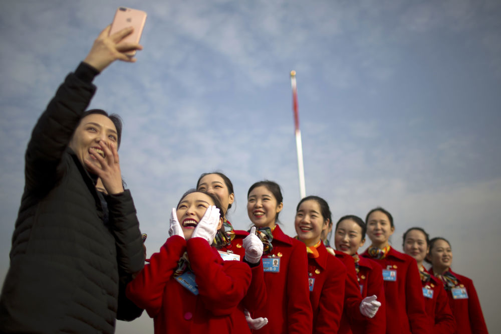 Сотрудницы гостиничного бизнеса снимают селфи во время сессии Всекитайского собрания народных представителей в Пекине