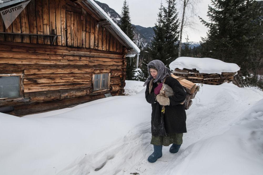 Отшельница из семьи староверов Агафья Лыкова идет с вязанкой дров