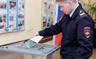 Сотрудник полиции опускает бюллетень в урну на выборах президента РФ на избирательном участке №51 в Петропавловске-Камчатском