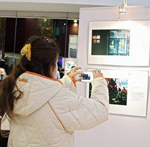 Посетительница на открытии выставки победителей конкурса имени Андрея Стенина
