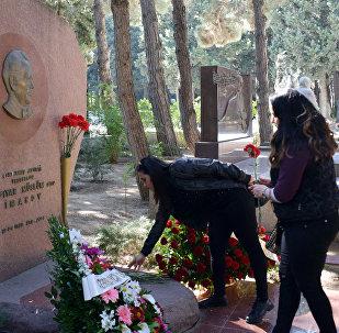Девушки возлагают цветы на могилу Лютфияра Иманова на Аллее почетного захоронения